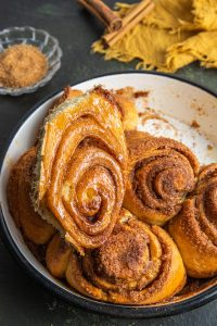 Baking dish with cinnamon rolls. One of them is taken out and placed on top of the other ones. Small glass ramekin with brown sugar on the back left side. Yellow napkin with cinnamon sticks on it at the far right back.