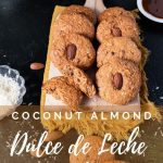Coconut almond dulce de leche cookies on a wooden cutting board with a yellow napkin under the board. Small plate with dulce de leche in it on the upper right side. Small glass bowl with shredded coconut on the left side next to the cutting board. Three cookies scattered in front of the board. Few almonds and shredded coconut sprinkled around. Little white vase with green plants peeking from the upper left corner.