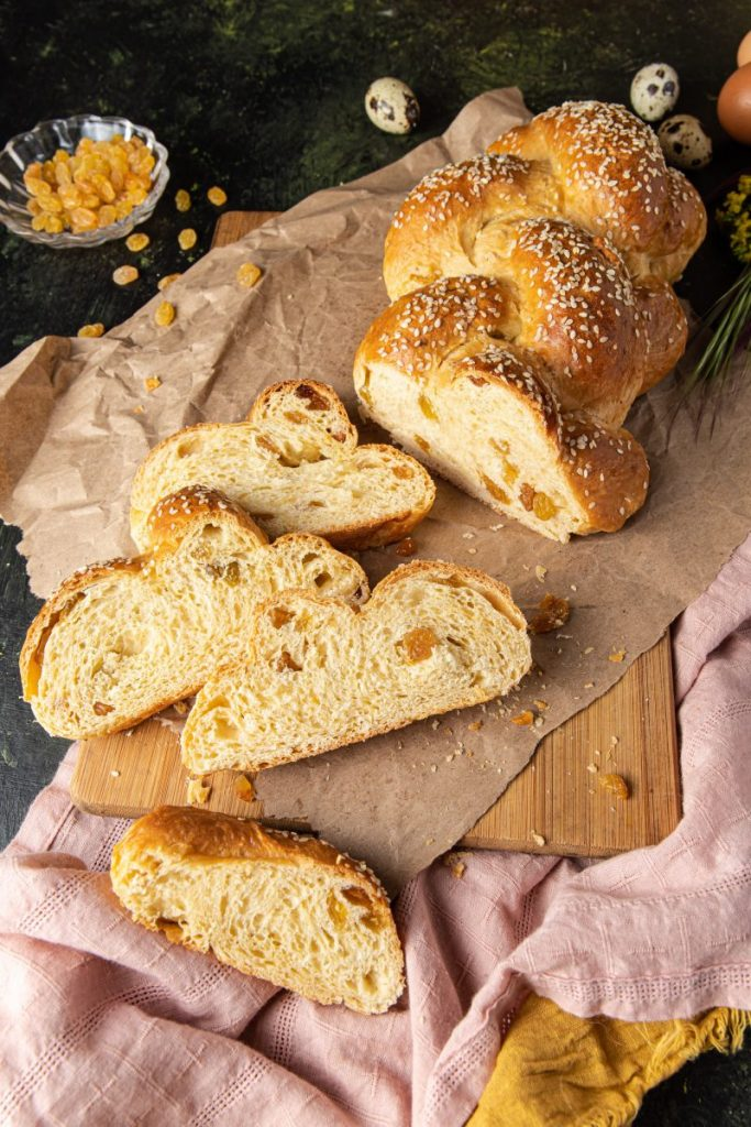 Braided bread with four slices on a brown paper on top of a wooden cutting board. Pink and yellow napkin underneath. Small glass bowl with golden raisins on the back left side with few raisins scattered around. Three quail eggs on the back behind the bread.