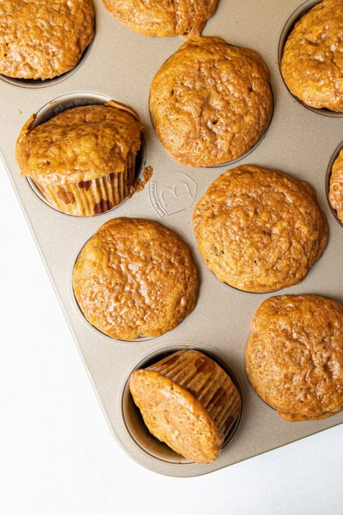 Muffin tray with muffins in it. Two of them are on its side.