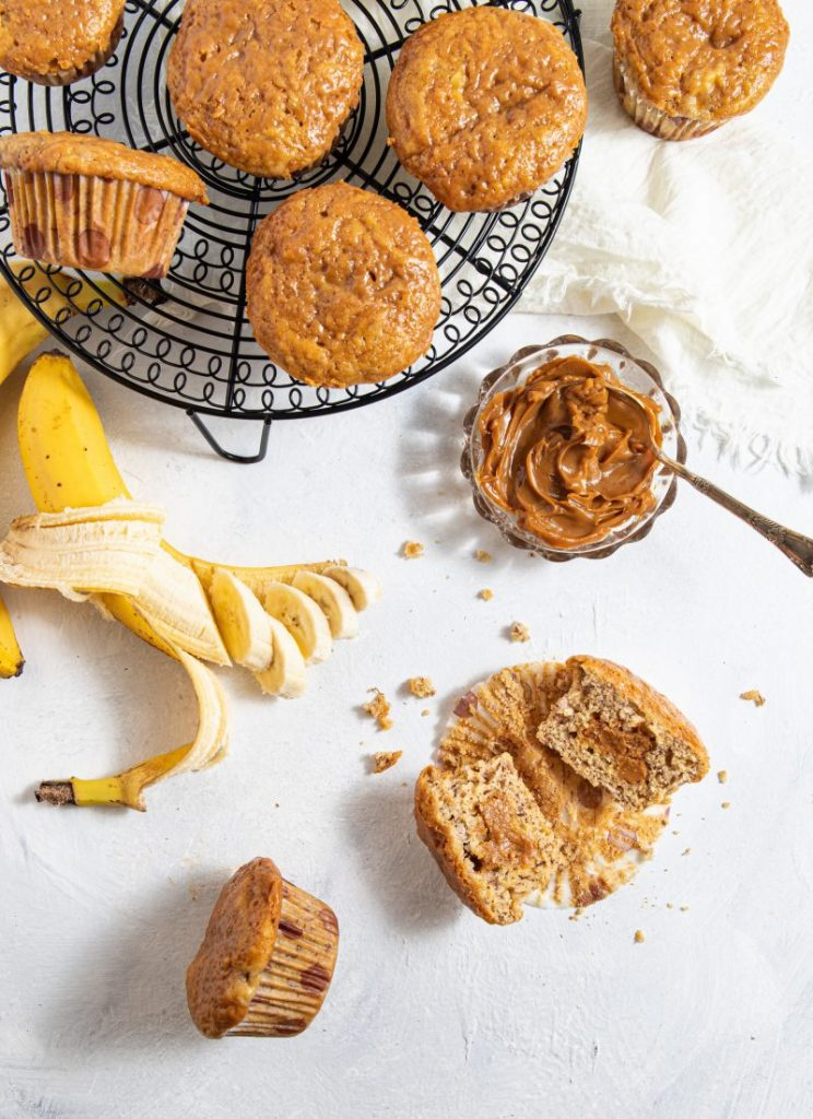 Muffins on a black round wire tray. On the left side one banana peeled half away and chopped into slices. On the right side white napkin laying next to the tray. Small glass bowl with dulce de leche and a spoon. One muffin cut in half on the lower right side with crumbs around it. One muffin on its side on the lower left side.