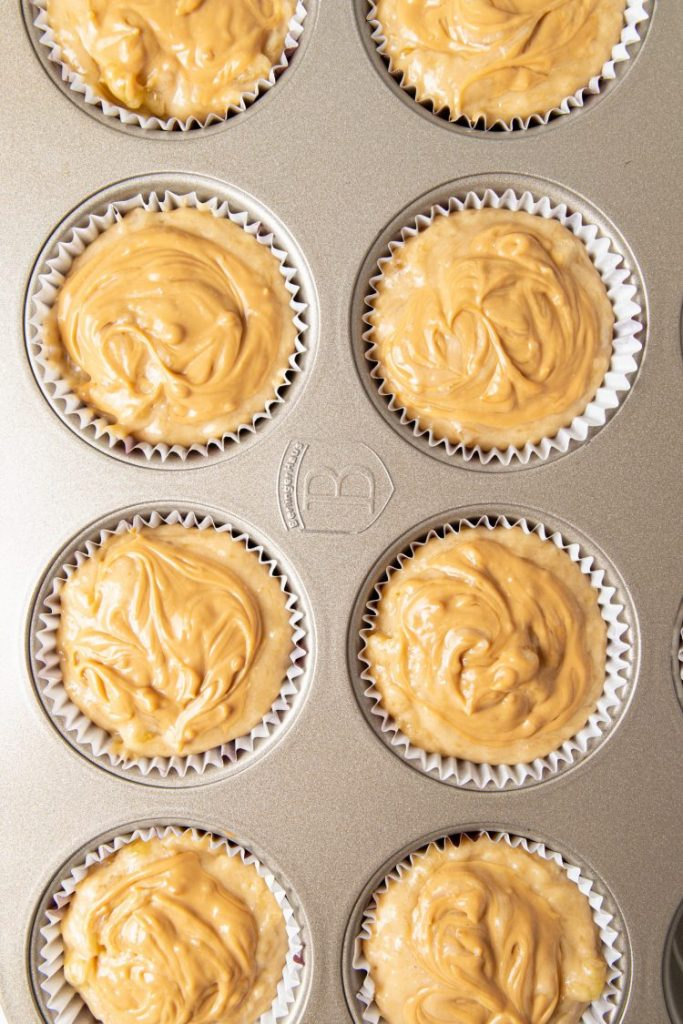 Muffin tray with paper cups filled with batter and topped with caramel-like cream on top, ready to bake.