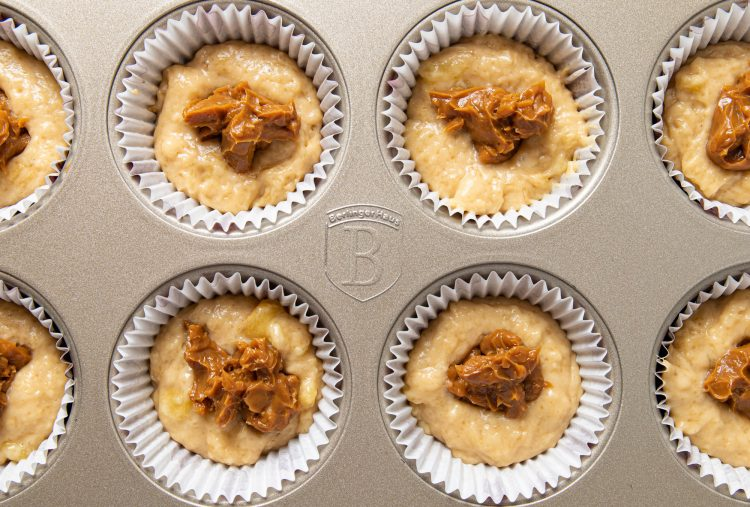 Muffin tray filled with paper cups, batter and dulce de leche in the center.