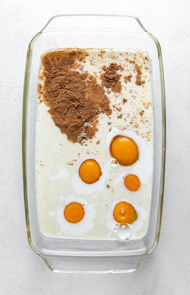 Rectangular glass dish filled with milk, eggs, cinnamon.