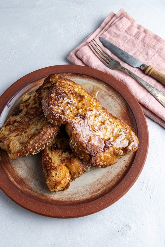 A plate with three pieces of french toast. Pink napkin on the side with fork and knife on it.