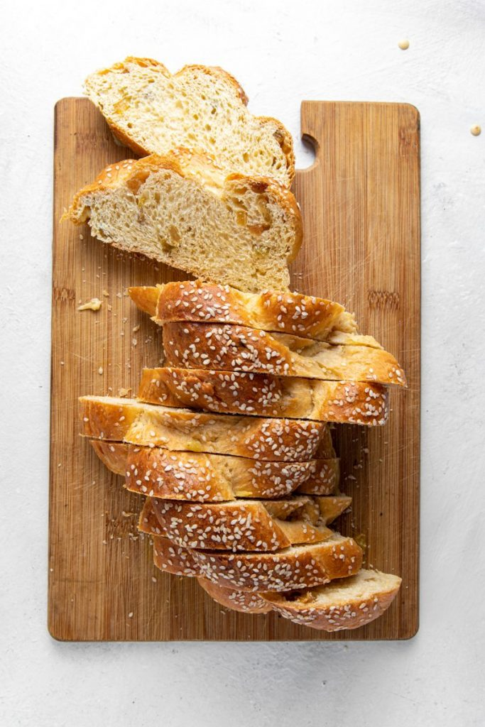 Wooden cutting board with sliced challah bread.