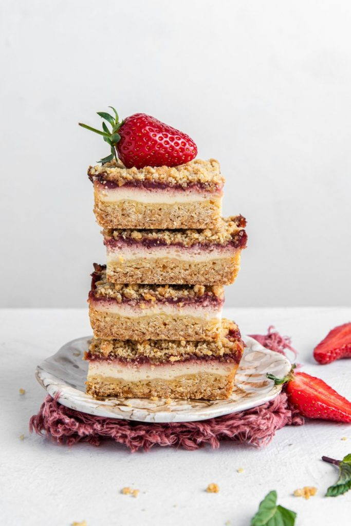 Four Strawberry Cream Cheese Bars stacked up one on top of each other with a strawberry on top. Sitting on a plate and a pink ruffed edges napkin under the plate. Sliced strawberry on the side, mint leaves and crumbs.