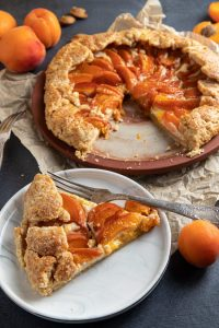 Apricot Ricotta Galette on a plate and a slice cut out. Small plate with the cut out slice and a fork. Baking paper under the plate. Fresh peaches scattered around