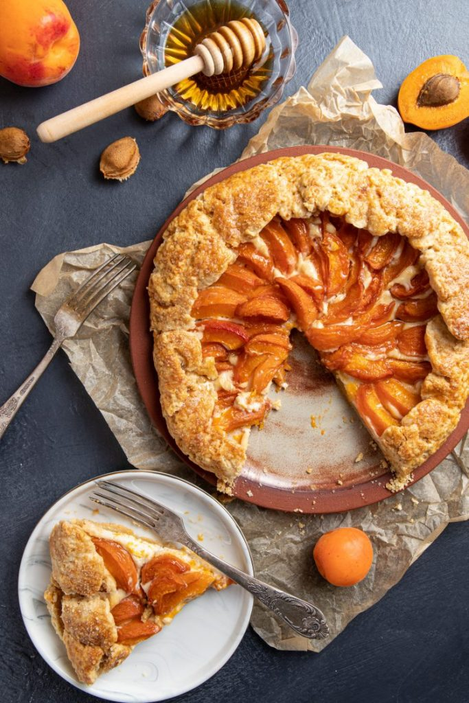 Apricot Ricotta Galette on a plate and a slice cut out. Small plate with the cut out slice and a fork next to the galette. Baking paper under the plate. Fresh peaches scattered around. Small glass ramekin with honey and honey spoon.
