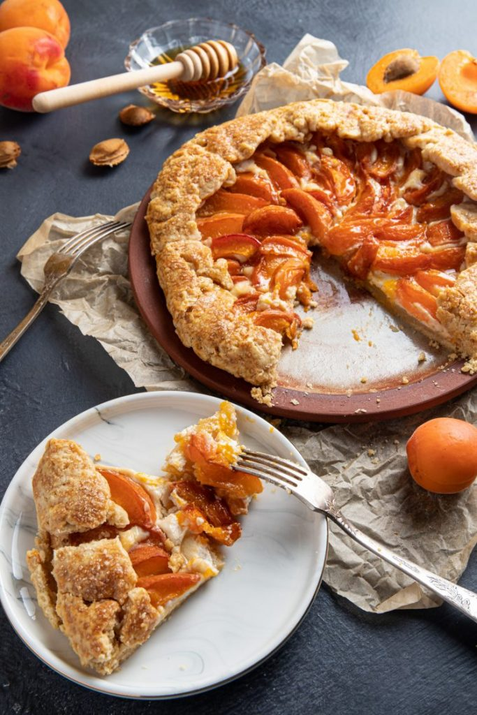 Apricot ricotta galette on a plate with a slice cut out. Small plate in front of the galette with the cut out slice. Fork with a piece of the galette on the plate. Wrinkled baking paper under the galette with fresh peaches scattered around. Small glass ramekin with honey and honey spoon.