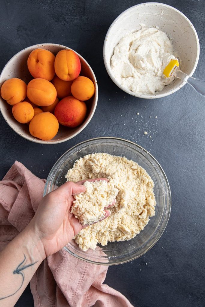A hand inside of a glass bowl showing the texture of a crumbly dough. A bowl with fresh apricots. Another bowl with ricotta and a spatula. Pink napkin next to the glass bowl.