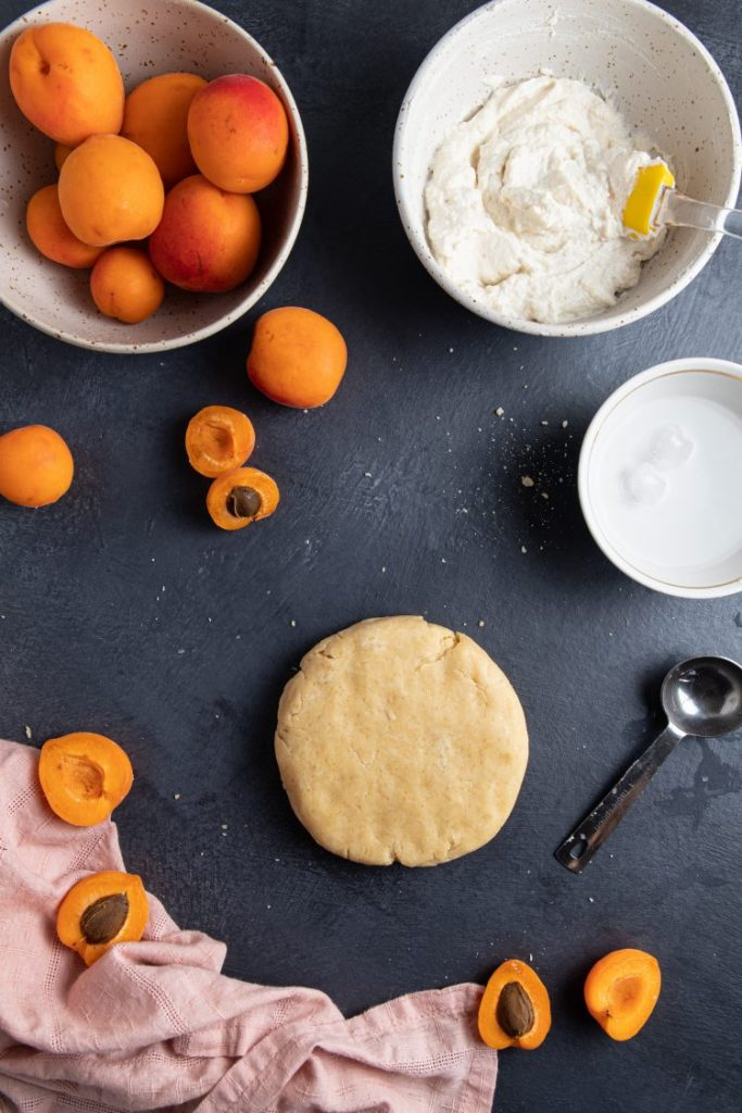 Flatten round dough at the center. A measuring spoon next to it. Small white bowl with water on the side. Bigger bowl with ricotta and a spatula on the upper right side. Another bowl with whole fresh apricots on the upper left side. Apricots scattered around. A pink napkin on the bottom left corner.