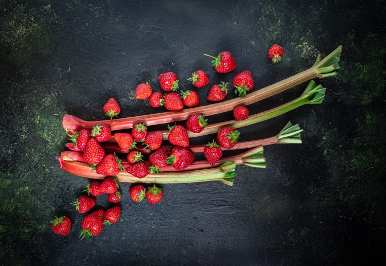 Rhubarb stalks with strawberries scattered on top.