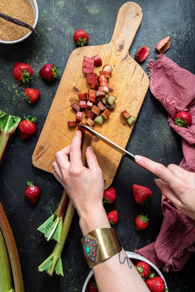 Two hand holding and cutting a rhubarb on a wooden cutting board. Strawberries scattered around. Pink napkin laying on the right side. Small bowl with brown sugar and vanilla bean on the top left corner.