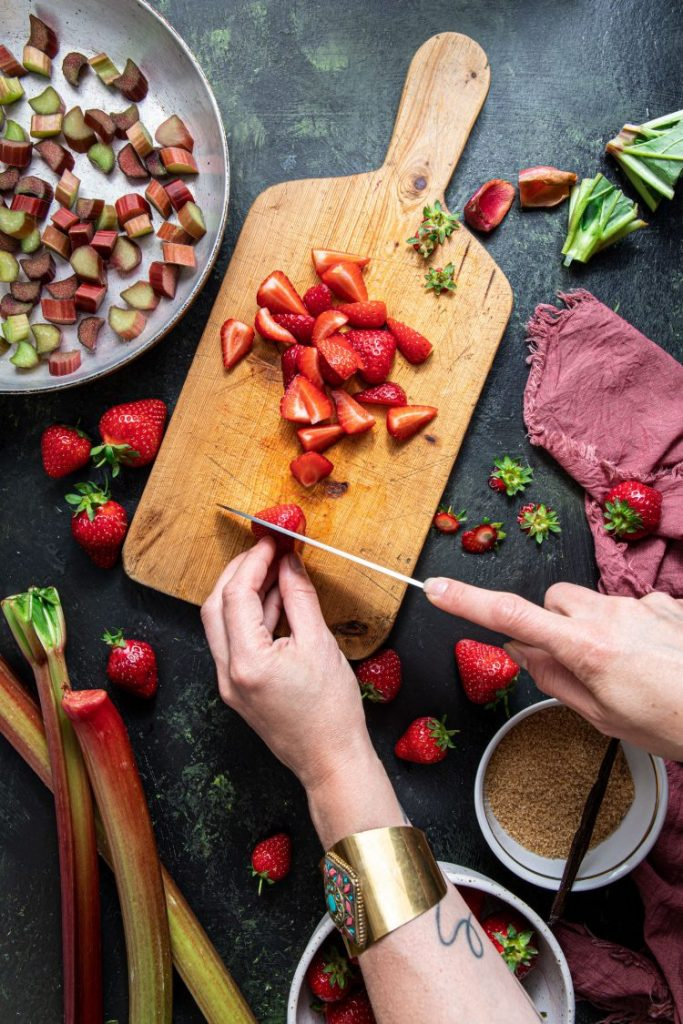 Two hand holding and cutting strawberries on a wooden cutting board. Strawberries scattered around. Pink napkin laying on the right side. Small bowl with brown sugar and vanilla bean between the hands. Rhubarb stalks on the left bottom corner. A pan with chopped rhubarb on the upper left corner.