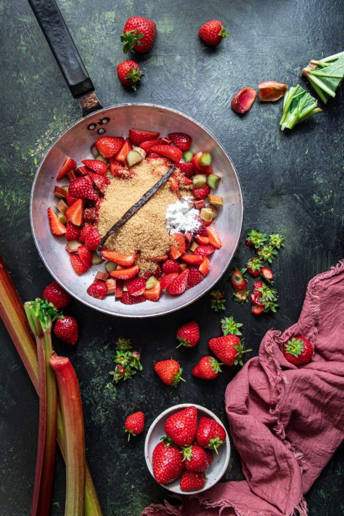 A pan filled with chopped strawberries and rhubarb, topped with light brown sugar, corn starch, and whole vanilla bean. Strawberries scattered around the pan. Pink napkin at the bottom right corner and a small bowl with strawberries next to it.