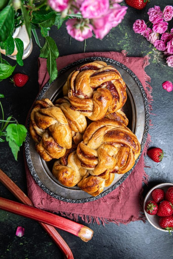 A plate with strawberry and rhubarb braided rolls. Small bowl with strawberries on the lower right side with more strawberries scattered around the plate. Two rhubarb stalks on the lower left side. Flowers peeking from the upper side.