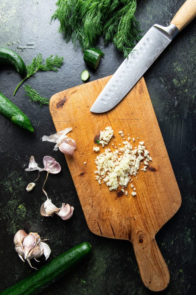 Cutting board with chopped garlic and a knife on it. Pieces of cucumbers, fresh dill, and garlic cloves on the left side of the cutting board.