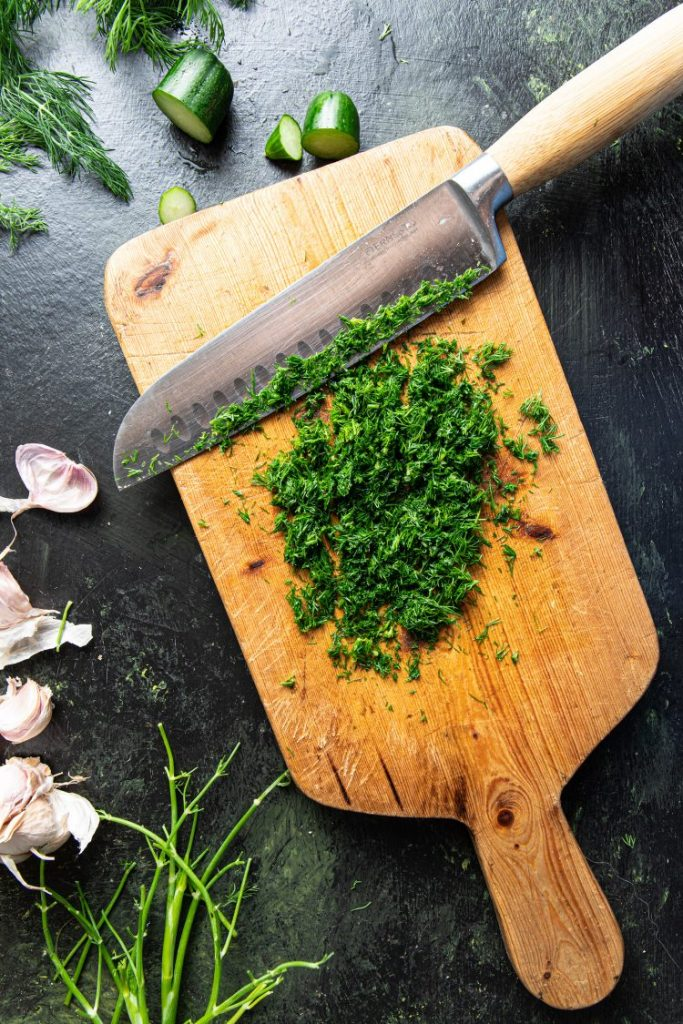 Cutting board with chopped dill and a knife on it. Pieces of cucumbers, fresh dill, and garlic cloves on the left side of the cutting board.