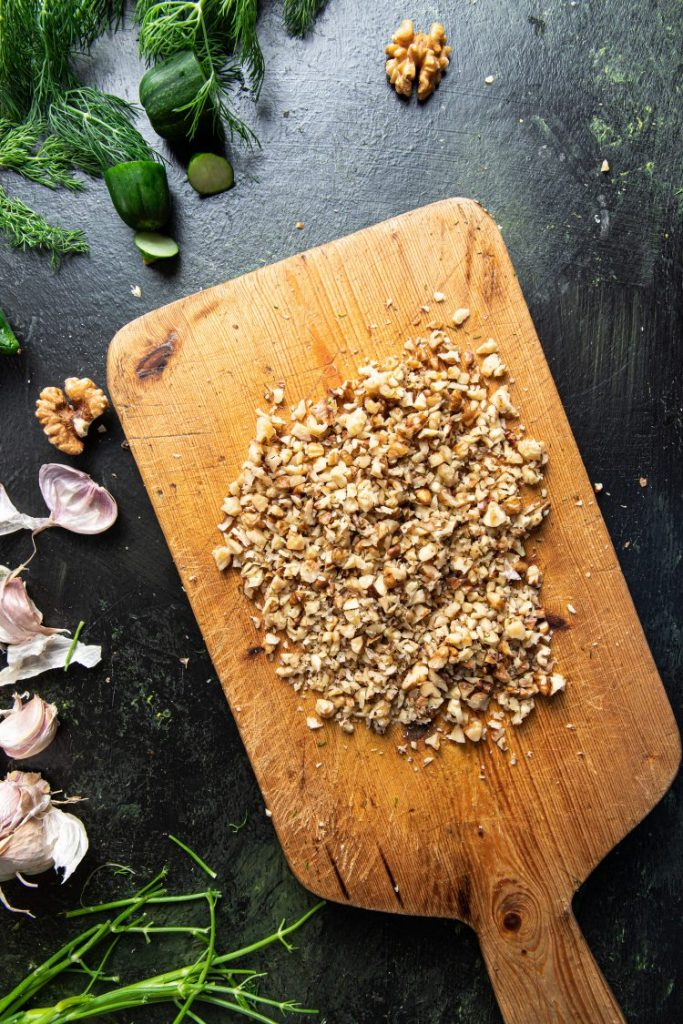 A wooden board with chopped walnuts. Pieces of walnuts, cucumbers, fresh dill, and garlic cloves on the left side of the cutting board.