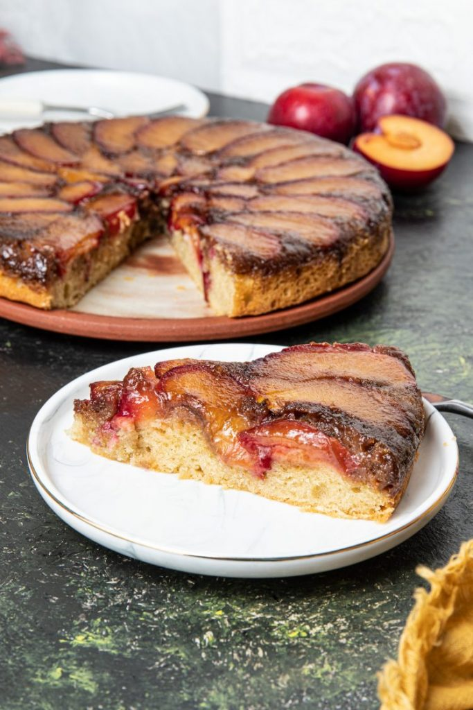 A slice of a plum upside-down cake on a plate. Cake with a slice cut out on the background. Fresh plums on the back right side.