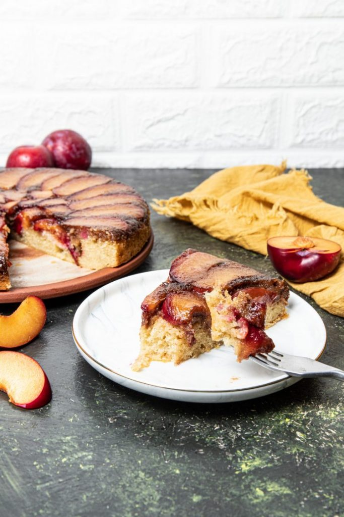 Slice of Upside-down plum cake on a plate with a fork leaning on the plate with a piece of cake. Cake on the back left side and fresh plums behind. Yellow napkin on the back right side with a half a plum on it.