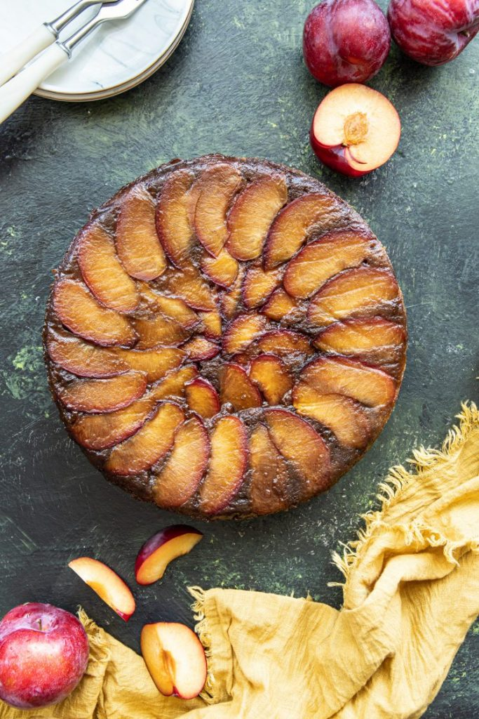 Overhead look of a Plum upside-down cake with fresh plums scattered around the cake. Yellow napkin at the lower side. Plate with two forks on the upper left corner.