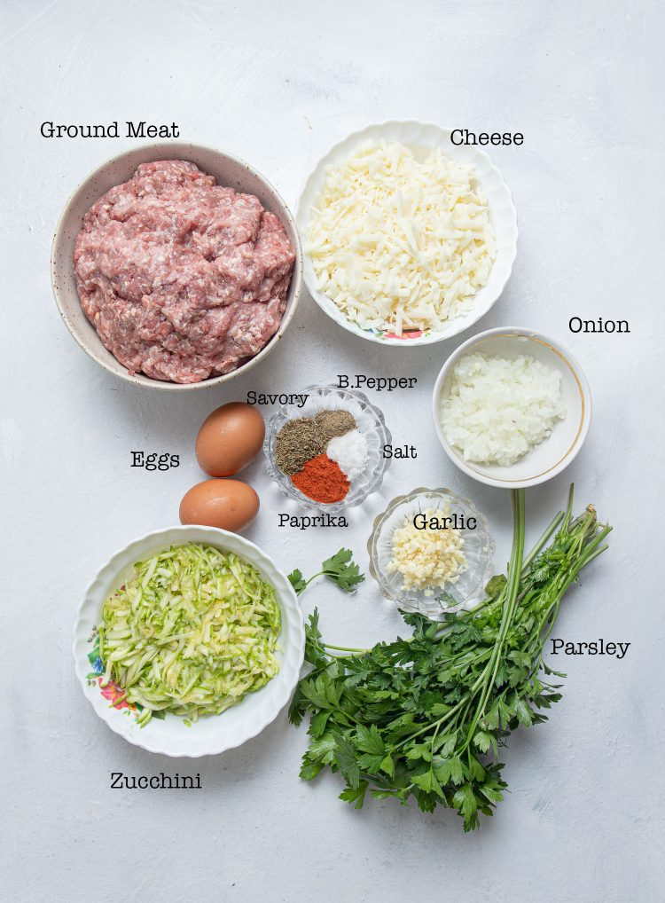 Bowl with ground meat, bowl with shredded cheese, bowl with chopped onion, bunch of parsley, small glass with chopped garlic, a bowl with shredded zucchini, two eggs, and a small bowl with salt, black pepper, savory, and paprika.