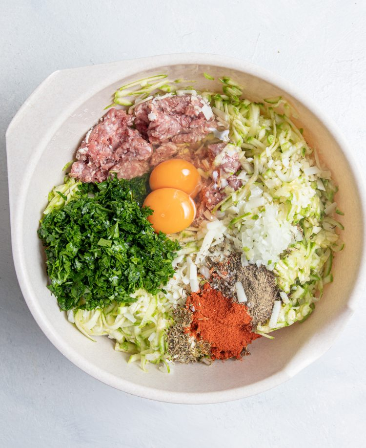 A bowl with ground meat, shredded zucchini, two eggs, chopped parsley, chopped onion, spices.