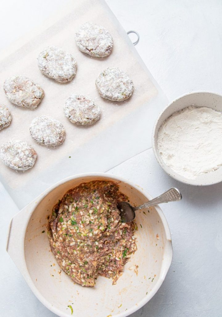 Meat patties formed in oval shape and covered with flour, arranged on a parchment paper. Bowl with flour on the right side. Bowl with meat patties mixture and a spoon in it.