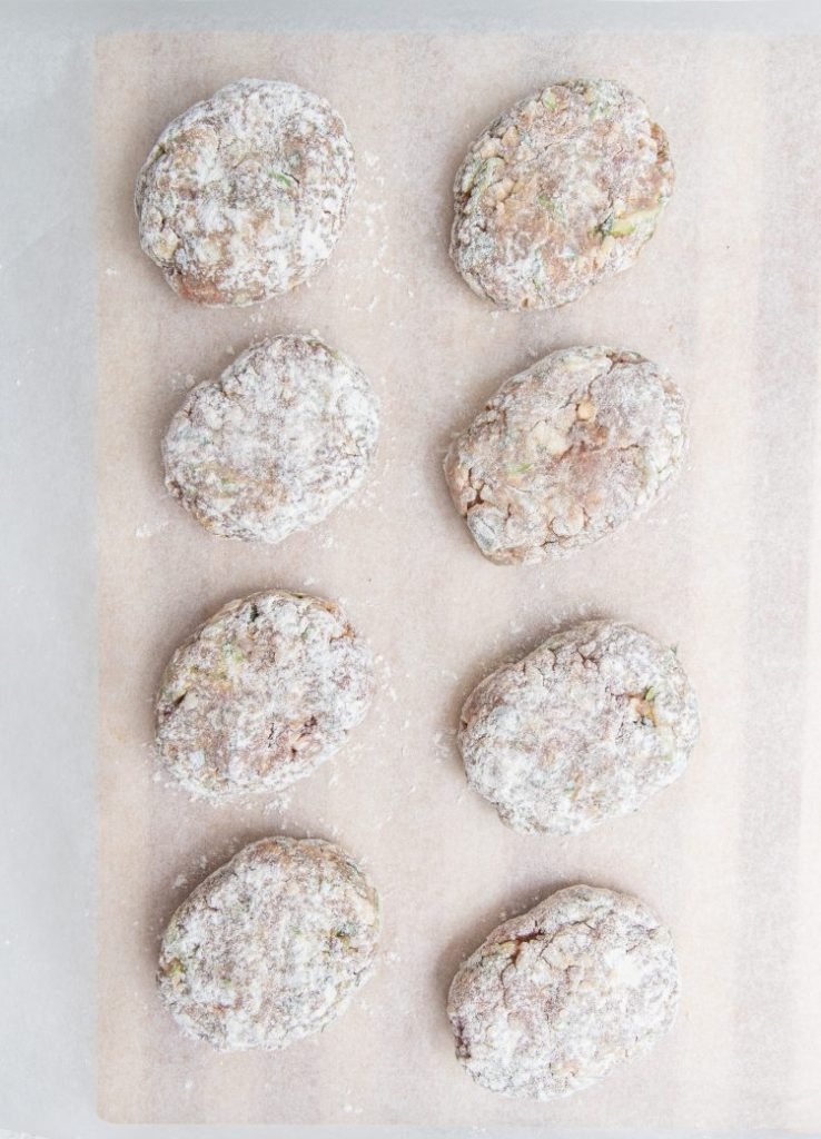 Eight meat patties covered with flour and arranged in two rows of four.