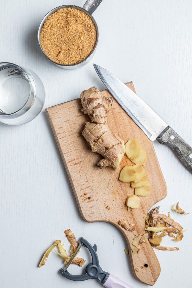 Wooden cutting board with a ginger and slices from it. A knife on the side. Ginger shavings around the board and a potato peeler. A measuring cup with a brown sugar in it. A glass with water next to the cutting board.